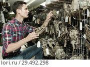 Купить «Man choosing holster for gun in military shop», фото № 29492298, снято 4 июля 2017 г. (c) Яков Филимонов / Фотобанк Лори