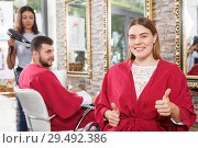 Купить «Smiling young woman client in salon's peignoir holding thumbs up», фото № 29492386, снято 25 апреля 2018 г. (c) Яков Филимонов / Фотобанк Лори