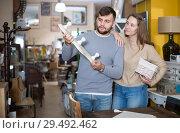 Купить «Cheerful couple looking for wall hanger», фото № 29492462, снято 9 ноября 2017 г. (c) Яков Филимонов / Фотобанк Лори