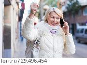 Купить «Happy female raise hand up and talking on phone», фото № 29496454, снято 21 декабря 2017 г. (c) Яков Филимонов / Фотобанк Лори