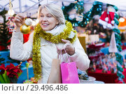 Купить «Woman is preparing for Christmas and choosing balls on the tree», фото № 29496486, снято 21 декабря 2017 г. (c) Яков Филимонов / Фотобанк Лори