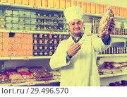 Купить «Salesman standing in food shop», фото № 29496570, снято 15 октября 2016 г. (c) Яков Филимонов / Фотобанк Лори