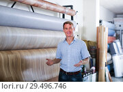 man choosing bolt of linoleum. Стоковое фото, фотограф Яков Филимонов / Фотобанк Лори
