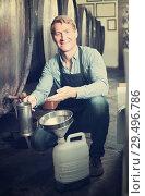 Купить «man pouring wine from wood in cellar», фото № 29496786, снято 18 декабря 2018 г. (c) Яков Филимонов / Фотобанк Лори