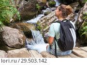 Купить «Женщина с рюкзаком отдыхает на камнях возле водопада», фото № 29503142, снято 27 июля 2018 г. (c) Кекяляйнен Андрей / Фотобанк Лори