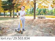 Купить «Little boy on scooter», фото № 29503834, снято 25 сентября 2015 г. (c) Сергей Сухоруков / Фотобанк Лори