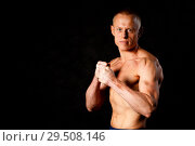 Купить «Muscular young man in studio on dark background shows the different movements and body parts», фото № 29508146, снято 29 октября 2018 г. (c) Иван Карпов / Фотобанк Лори