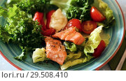 Купить «Image of plate with fried trout, egg, vegetables and green lettuce at table», видеоролик № 29508410, снято 27 сентября 2018 г. (c) Яков Филимонов / Фотобанк Лори