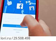 Купить «Вход в мобильную версию Facebook. Телефон в руке», фото № 29508498, снято 1 декабря 2018 г. (c) Екатерина Овсянникова / Фотобанк Лори