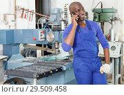 Купить «Workman having phone conversation», фото № 29509458, снято 16 мая 2018 г. (c) Яков Филимонов / Фотобанк Лори