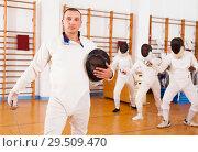 Купить «Man fencer in uniform with mask and foil», фото № 29509470, снято 11 июля 2018 г. (c) Яков Филимонов / Фотобанк Лори