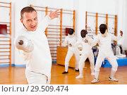 Купить «Sporty young man fencer practicing effective fencing techniques in training room», фото № 29509474, снято 11 июля 2018 г. (c) Яков Филимонов / Фотобанк Лори