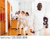 Купить «Active african american male fencer in uniform standing with mask and foil at fencing room», фото № 29509494, снято 11 июля 2018 г. (c) Яков Филимонов / Фотобанк Лори