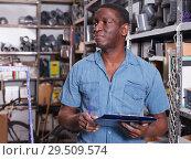 Купить «Ordinary African American male making inventory», фото № 29509574, снято 12 апреля 2018 г. (c) Яков Филимонов / Фотобанк Лори