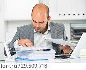 Купить «Businessman in shirt viewing documents at the table», фото № 29509718, снято 3 мая 2017 г. (c) Яков Филимонов / Фотобанк Лори
