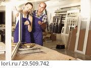 Купить «Two workers in blue overalls assembling pvc windows», фото № 29509742, снято 19 июля 2017 г. (c) Яков Филимонов / Фотобанк Лори