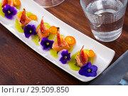 Купить «Ceviche from pickled red fish and cumquat a circle of kiwi, with figs at plate», фото № 29509850, снято 19 апреля 2019 г. (c) Яков Филимонов / Фотобанк Лори