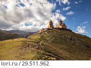 Купить «Gergeti Trinity Church on top of mountain against the sky, Georgia», фото № 29511962, снято 24 сентября 2018 г. (c) Юлия Бабкина / Фотобанк Лори