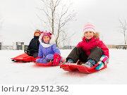 Купить «happy little kids sliding on sleds in winter», фото № 29512362, снято 10 февраля 2018 г. (c) Syda Productions / Фотобанк Лори