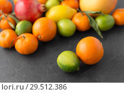 Купить «close up of citrus fruits on stone table», фото № 29512386, снято 4 апреля 2018 г. (c) Syda Productions / Фотобанк Лори