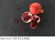 Купить «close up of pomegranate on stone table», фото № 29512642, снято 4 апреля 2018 г. (c) Syda Productions / Фотобанк Лори
