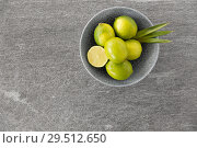 Купить «close up of whole limes in bowl», фото № 29512650, снято 4 апреля 2018 г. (c) Syda Productions / Фотобанк Лори