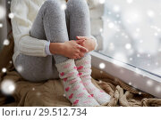 Купить «girl sitting on sill at home window in winter», фото № 29512734, снято 5 ноября 2016 г. (c) Syda Productions / Фотобанк Лори