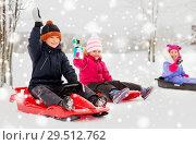 Купить «happy little kids sliding on sleds in winter», фото № 29512762, снято 10 февраля 2018 г. (c) Syda Productions / Фотобанк Лори