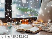 Купить «book, garland lights and candles on window sill», фото № 29512902, снято 15 ноября 2017 г. (c) Syda Productions / Фотобанк Лори