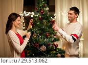 Купить «happy couple decorating christmas tree at home», фото № 29513062, снято 11 января 2018 г. (c) Syda Productions / Фотобанк Лори