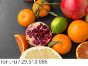 Купить «close up of citrus fruits on stone table», фото № 29513086, снято 4 апреля 2018 г. (c) Syda Productions / Фотобанк Лори