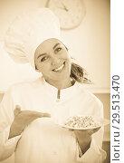 Купить «Girl cook shows plate of porrige», фото № 29513470, снято 11 декабря 2018 г. (c) Яков Филимонов / Фотобанк Лори
