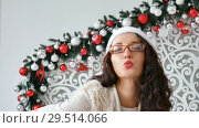 Купить «Beautiful young woman wearing santa claus hat and glasses for Chritmas celebration event. Attractive female being silly, making faces at dress up party. Background, close up, copy space», видеоролик № 29514066, снято 3 декабря 2018 г. (c) Ольга Балынская / Фотобанк Лори