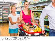Купить «Positive family with teen daughter and purchases in shopping», фото № 29523074, снято 11 июля 2017 г. (c) Яков Филимонов / Фотобанк Лори