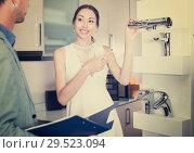 Купить «Beautiful woman choosing mixer tap in kitchen accessories store», фото № 29523094, снято 15 июня 2017 г. (c) Яков Филимонов / Фотобанк Лори