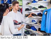 Купить «Young couple choosing new sneakers in sports store», фото № 29523190, снято 22 ноября 2016 г. (c) Яков Филимонов / Фотобанк Лори