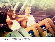 Купить «Well trained friendly young man and woman training abdominal muscles in gym», фото № 29523226, снято 4 октября 2016 г. (c) Яков Филимонов / Фотобанк Лори