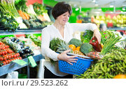 Купить «Adult female taking vegetables with basket», фото № 29523262, снято 10 марта 2017 г. (c) Яков Филимонов / Фотобанк Лори