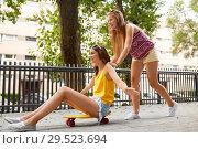 Купить «teenage girls riding skateboard on city street», фото № 29523694, снято 19 июля 2018 г. (c) Syda Productions / Фотобанк Лори