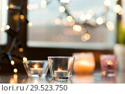 Купить «candles burning on window sill with garland lights», фото № 29523750, снято 13 января 2018 г. (c) Syda Productions / Фотобанк Лори