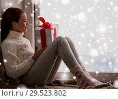 Купить «girl with christmas gift sitting on sill at window», фото № 29523802, снято 5 ноября 2016 г. (c) Syda Productions / Фотобанк Лори