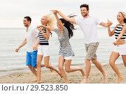 Купить «friends in striped clothes running along beach», фото № 29523850, снято 13 июля 2014 г. (c) Syda Productions / Фотобанк Лори