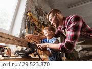 Купить «father and son with rasp working at workshop», фото № 29523870, снято 14 мая 2016 г. (c) Syda Productions / Фотобанк Лори