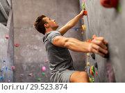 Купить «young man exercising at indoor climbing gym», фото № 29523874, снято 2 марта 2017 г. (c) Syda Productions / Фотобанк Лори