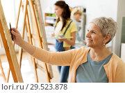 Купить «senior woman drawing on easel at art school studio», фото № 29523878, снято 26 мая 2017 г. (c) Syda Productions / Фотобанк Лори