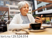 Купить «happy senior woman with smartphone at street cafe», фото № 29524014, снято 3 августа 2018 г. (c) Syda Productions / Фотобанк Лори