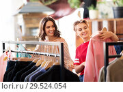 Купить «women choosing clothes at vintage clothing store», фото № 29524054, снято 7 августа 2018 г. (c) Syda Productions / Фотобанк Лори