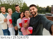 Купить «friends with drinks taking selfie at rooftop party», фото № 29524070, снято 2 сентября 2018 г. (c) Syda Productions / Фотобанк Лори