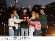 Купить «friends clinking party cups on rooftop at night», фото № 29524074, снято 2 сентября 2018 г. (c) Syda Productions / Фотобанк Лори