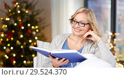 Купить «woman in glasses reading book on christmas», фото № 29524370, снято 27 ноября 2015 г. (c) Syda Productions / Фотобанк Лори